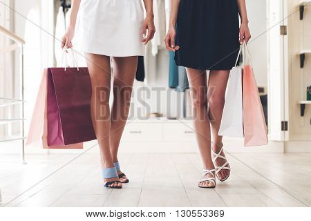 Shopping time! Close-up part of two women with perfect legs holding shopping bags while walking at the store