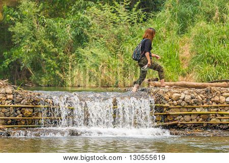 PAI, THAILAND - April 13, 2016 : a woman walking on the small weir irrigate at Wang Pla in Pai Thailand