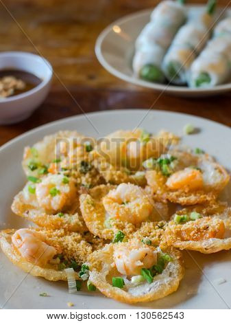 Banh Khot with shrimps miniature fried pancakes served in Vietnam. Goi cuon Vietnamese spring rolls in the background. Very shallow depth of field with the first pancake in focus