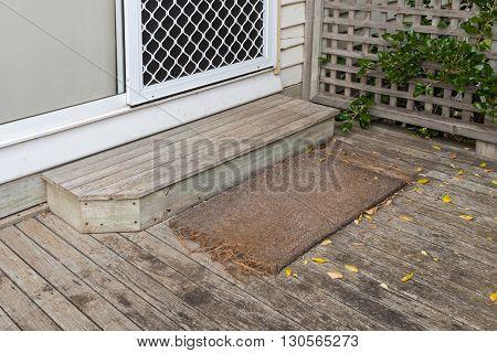 Old plain coir doormat placing in front of the doorstep at back door during Autumn