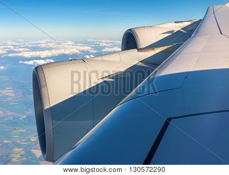 Wing with engines of Airbus A380 airliner flying over clouds poster