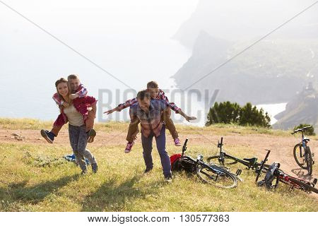 Family of four people with bikes in the mountains