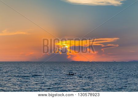 Dramatic sun lights background over seacoast during sunset