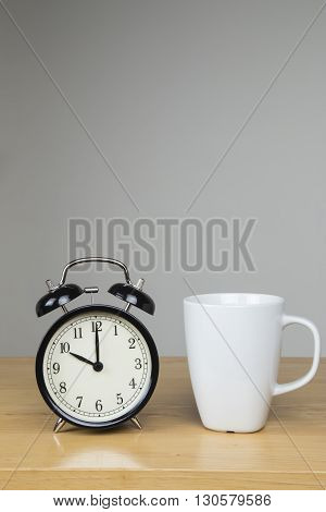 Cup of tea and alarm clock on desk