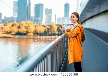 Young sport woman in yellow sweater using smart phone on the modern bridge with skyscrapers on the background. Morning exercise in megacity