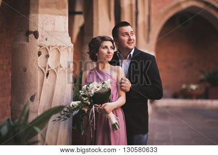 Young couple in love bride and groom posing near area with white columns on the background. Krakow.