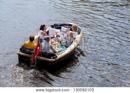 Amsterdam, Netherlands - May 5: The family of the residents of the Netherlands celebrate Independence Day on the river Amstel on the boat