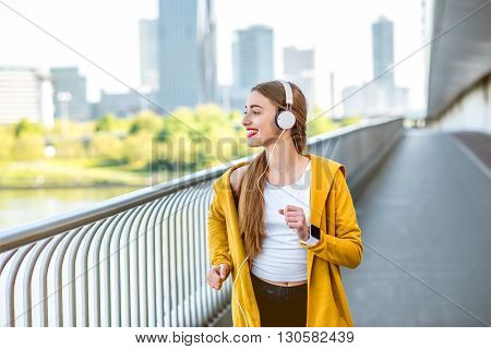 Young sport woman in yellow sweater with earphones running on the modern bridge with skyscrapers on the background. Morning exercise in megacity