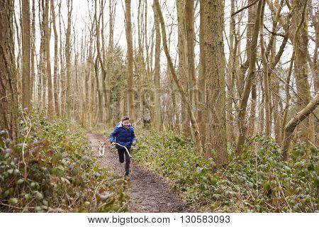 Boy holding stick running through a wood followed by pet dog