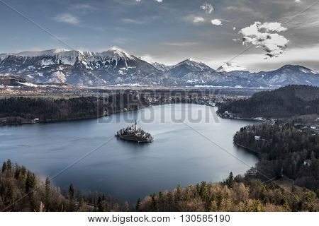 Panoramic view of island with church in the middle of Lake Bled among the mountains in snow.