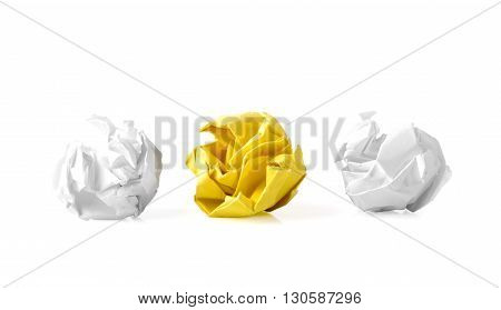 Yellow paper ball between two white ones as a symbol of difference and variety of society and ideas.