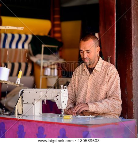 MARRAKECH MOROCCO - NOVEMBER 04 2015: A man sitting at his sewing machine at a fabric shop in the souk of Marrakech in Morocco.