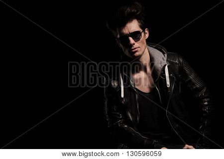portrait of an attractive man in leather jacket posing in studio