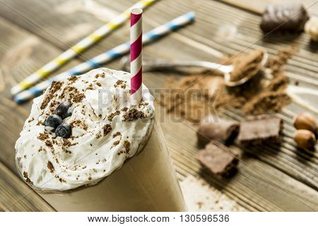 Milk chocolate drink with a straw on a background of cocoa and chocolate