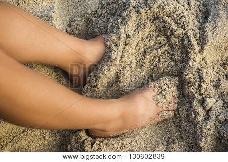 A tan woman's legs in wet sand