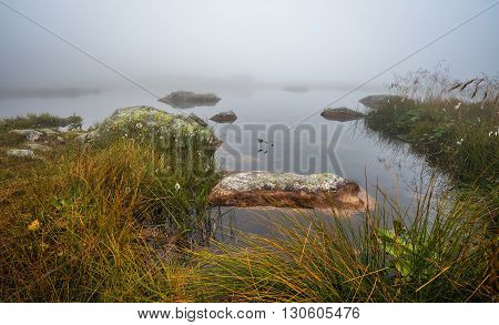 Small Tarn with Rocks on Foggy Morning