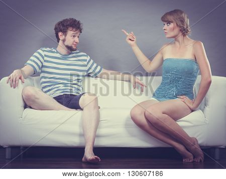 Bad relationship concept. Man and woman in disagreement. Young couple sitting on couch at home having quarrel filtered photo
