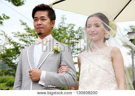 KAGAWA, JAPAN - MAY 15, 2016: Beautiful Japanese wedding couple wedding in Zentuji-Gogakunosato Park. Young wedding couple, beautiful bride with groom portrait.
