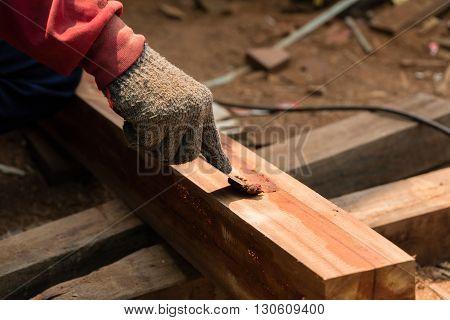 Man caulking on the cracks lumber by Glue sawdust
