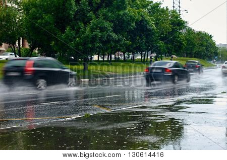 cars driving in the rain on a wet road. cars are in the motion but focus is on the road
