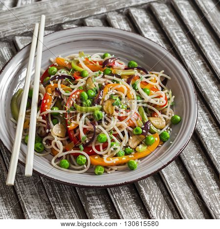 Rice noodles with vegetable stir fry on the ceramic plate on wooden background