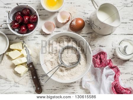 Baking rustic light background. Raw ingredients for baking pie with cherries - flour eggs milk sugar butter cream cherries. Rustic style