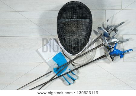 Fencing foil equipment. Three fencing foils with pistol grip (sporting weapon) a fencing mask and a blue and white glove on floor.