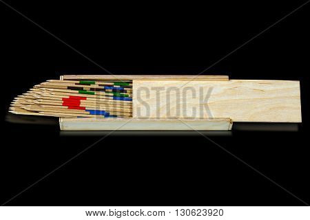 Game of mikado or shanghai with wooden sticks and box isolated on black background
