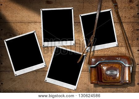 Old and vintage camera with leather case and four empty instant photo frames on a wooden wall