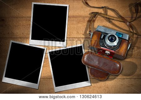 Old and vintage camera with leather case and three empty instant photo frames on a wooden table