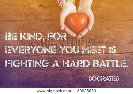 Be kind for everyone you meet - ancient Greek philosopher Socrates quote printed on image of hahds with heart