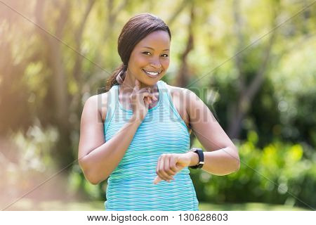 Happy woman looking her watch at park