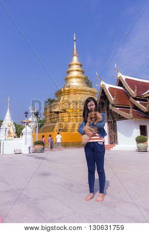 Thai woman with pomeranian at Wat Phra That Si Chom Thong Worawihan pagoda poster