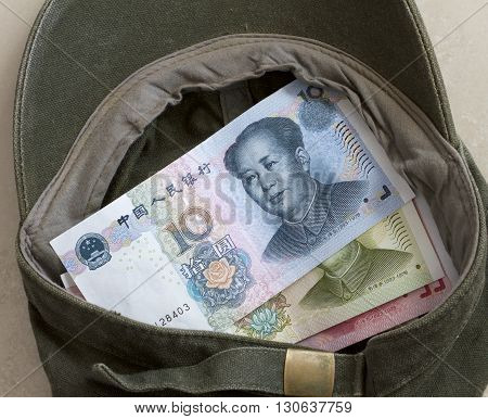 Chinese renminbi notes in a busker's cap. poster