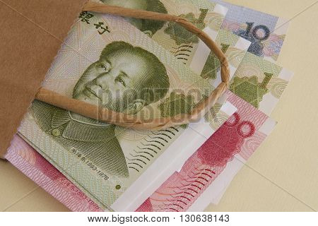 Chinese yuan or renminbi (rmb) currency in a brown paper bag.