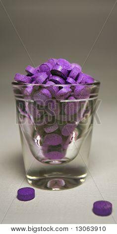 Purple Pills in Shot Glass