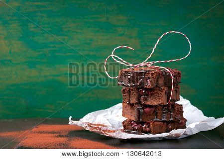 Homemade chocolate sweet brownies cakes with cherry and chocolate sauce or syrup on a dark background horizontal with place for text