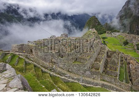 View of the Lost Incan City of Machu Picchu near Cusco.Low clouds cover mountains.Cusco RegionSacred Valley Peru