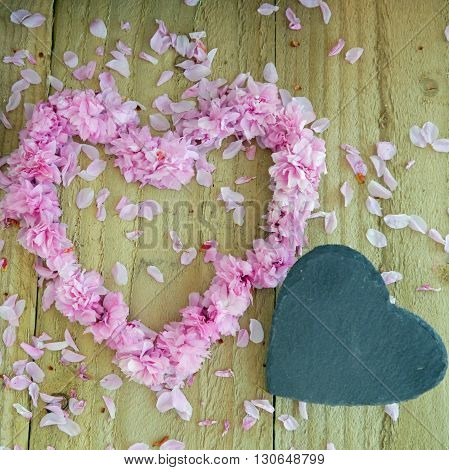 Pink blossom heart and black slate hearts. Space for text