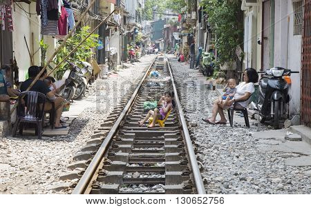 Hanoi, Vietnam - May 21, 2016: Usual life with some Vietnamese sitting right on the railroad and houses on the railway track. It's dangerous to live here but people don't have many choices.