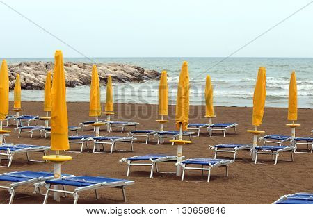 Yellow Closed Sun Umbrellas On Sea Beach With Sun Loungers