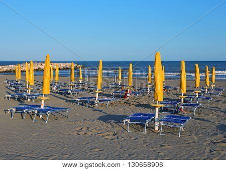 Sun Umbrellas On Sea Beach With Sun Loungers And Deckchairs