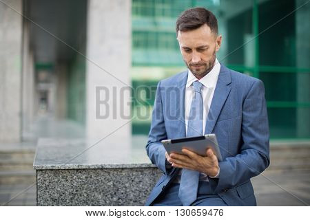 successful middle aged man working with tablet
