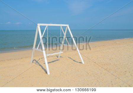 White swing on the sand beach. Pastel