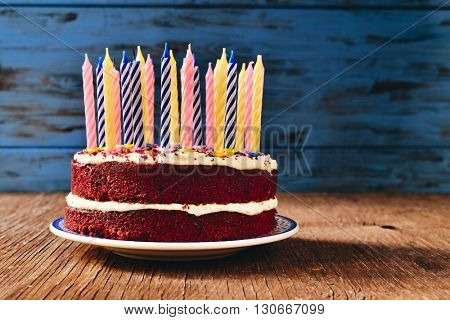 a red velvet cake topped with some unlit candles on a rustic wooden table poster