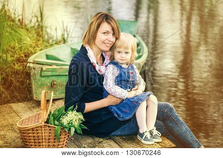Mom And Adorable Small Daughter Playing Together In Old Wooden Boat On River
