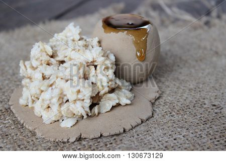 Cooked oatmeal on clay plate and the jar of honey on a background of llano tissue.
