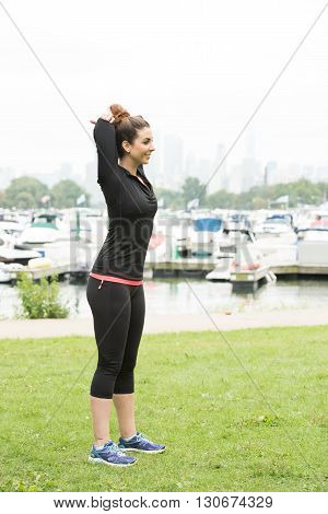 A beautiful and healthy girl doing pre exercie in a trendy sportswear inside a park in the early morning. A few boats is seen in the background of the image.