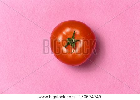 Top view of red tomato on a pink background. Fresh tomato. Appetizing red tomato. Beauty red tomato. Creative photo of tomato in center. Vegetable texture. Tomato menu. Tomato poster.