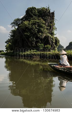 Female tourist riding on boat whilst the trip to Tam Coc caves in Hoa Lu capital located in Ninh Binh. On the background limestone karst mountains are seen covered by lush greeneries.